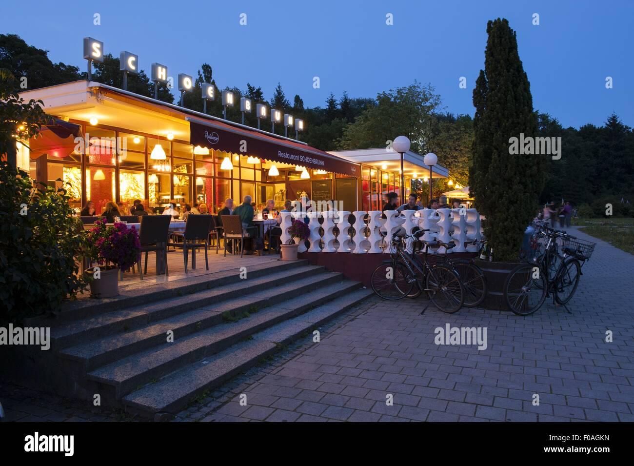 People at restaurant Schonbrunn at night in Volkspark Friedrichshain, Berlin, Germany - Stock Image