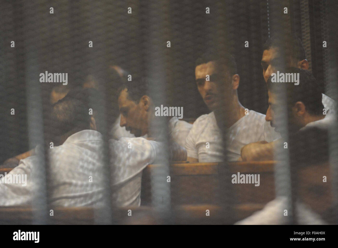 Cairo, Egypt. 11th Aug, 2015. Egyptian defendants sit behind bars during their trial over a 2012 stadium riot in Stock Photo