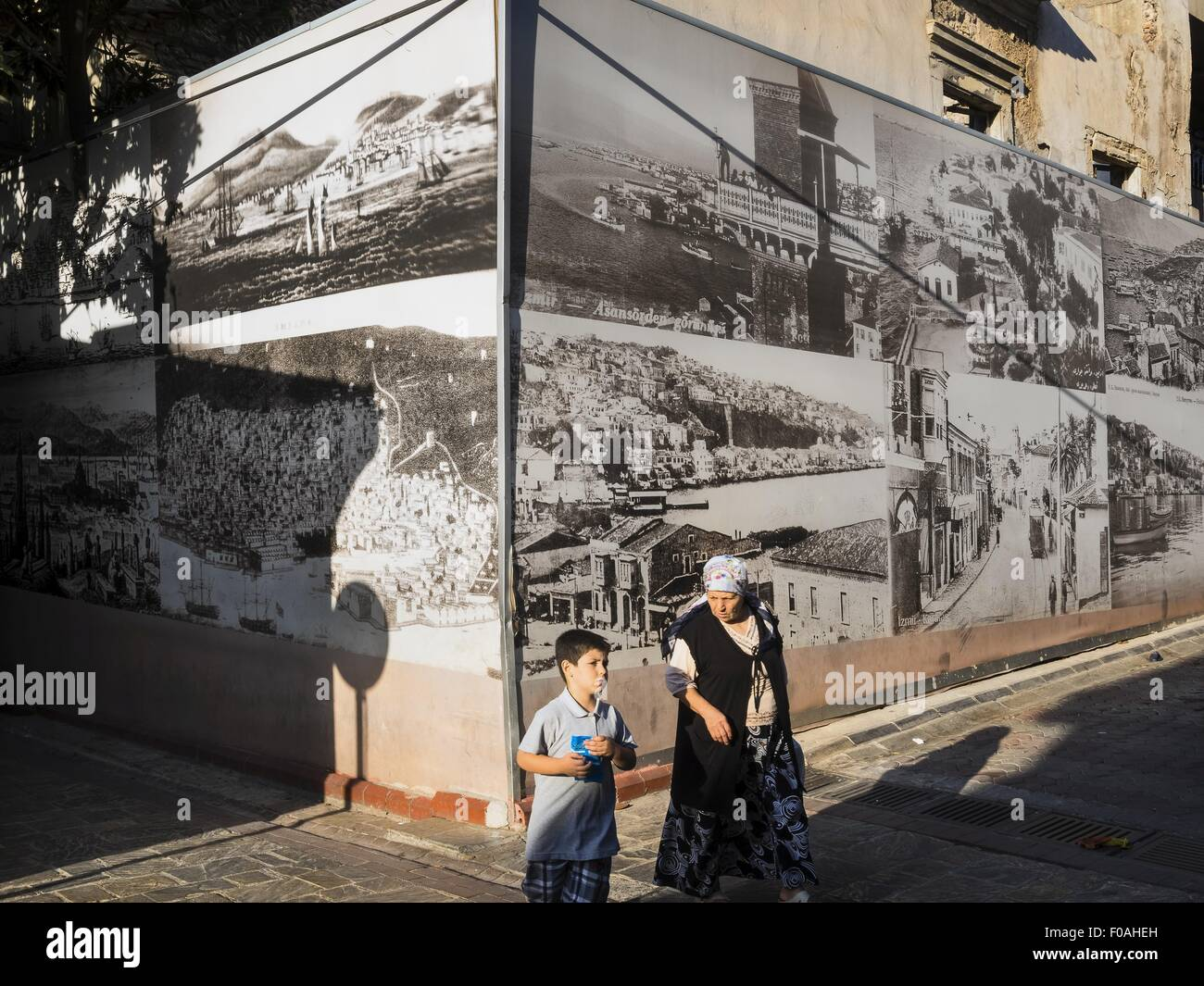 Woman and child walking in front of historical photos on Asansor in Aegean Region, Turkey - Stock Image