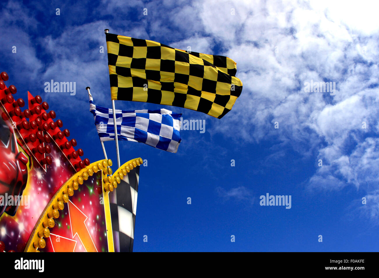 Chequered flags against a summer sky - Stock Image