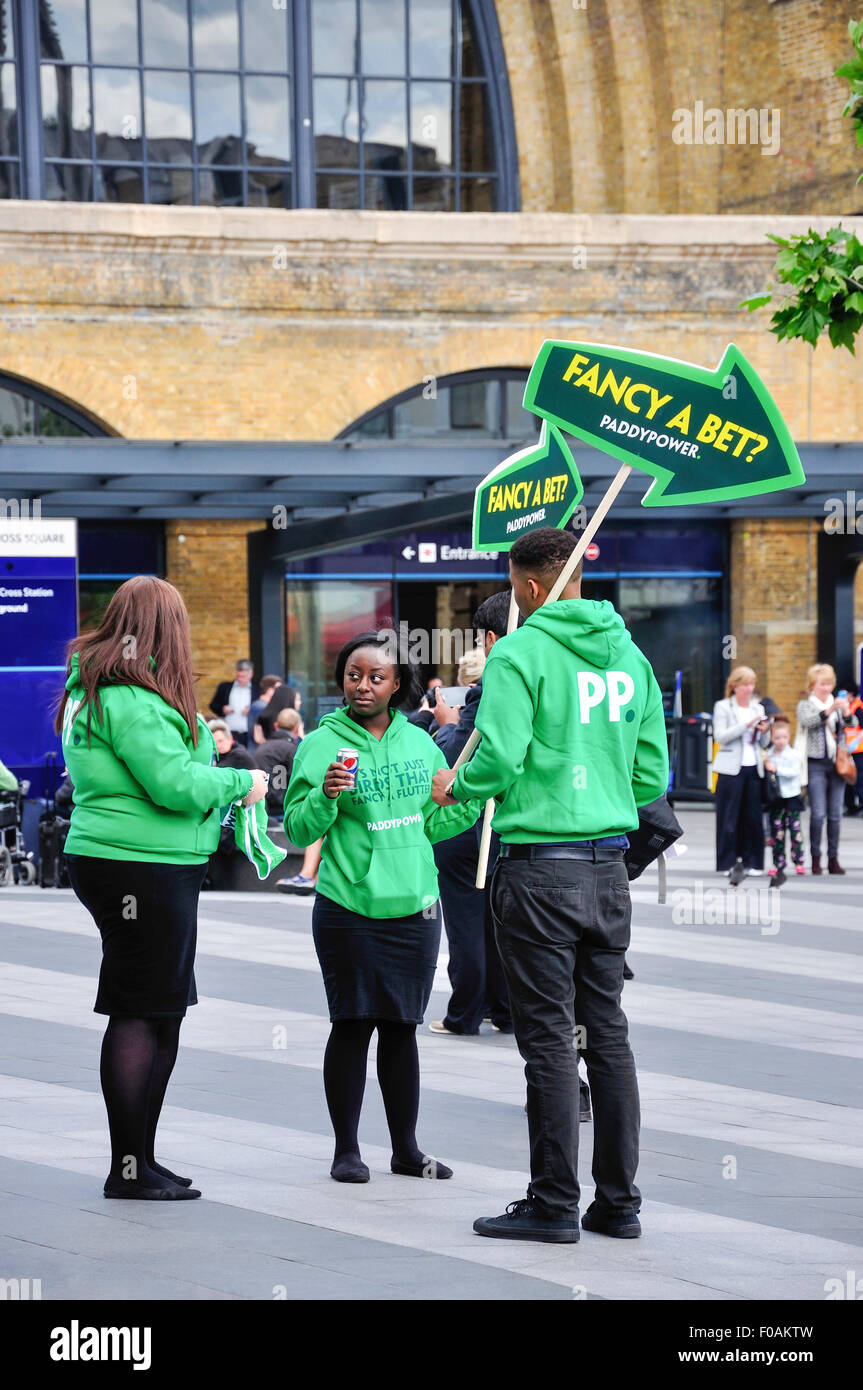 Young 'PaddyPower' team with signs outside King's Cross railway station, King's Cross, London Borough of Camden, Stock Photo