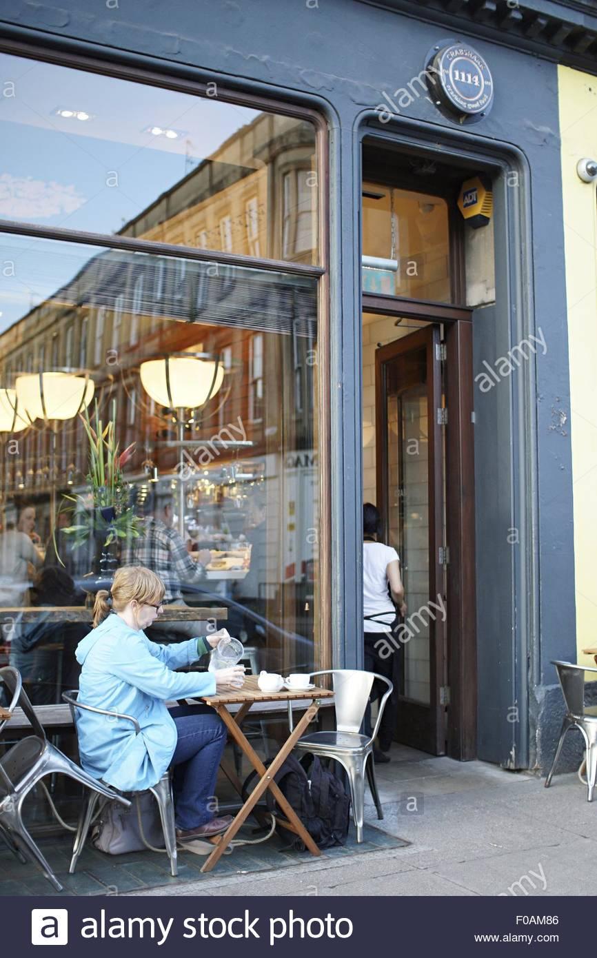 Woman sitting at table outside Crabshakk Restaurant, Glasgow, Scotland, UK - Stock Image