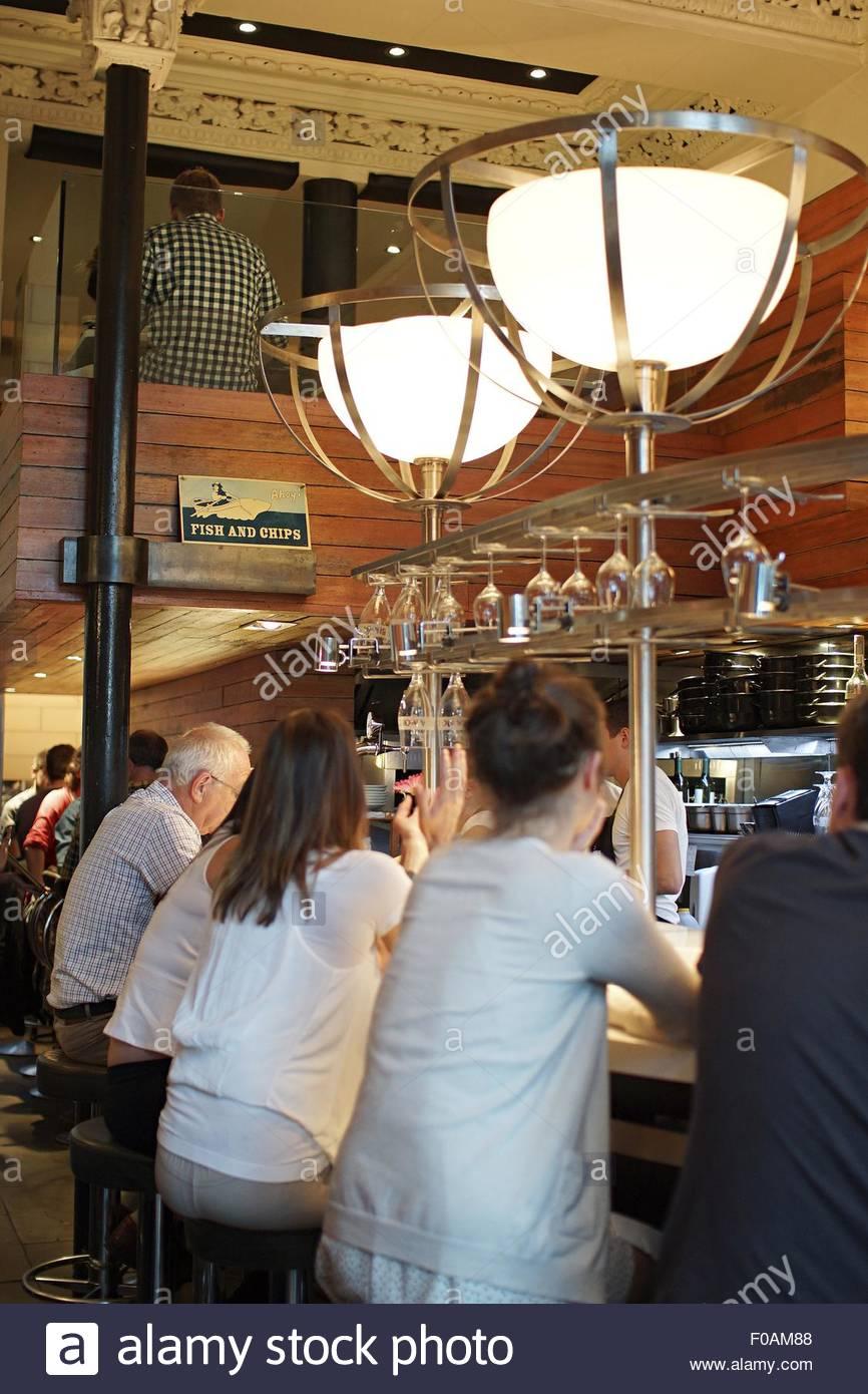 People sitting at bar counter in Crabshakk Restaurant, Glasgow, Scotland, UK - Stock Image