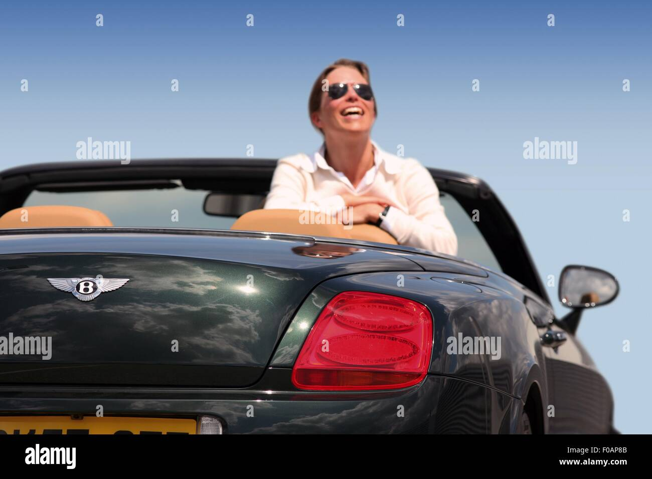 Happy woman in black Bentley GTC wearing sunglass, looking up and laughing - Stock Image