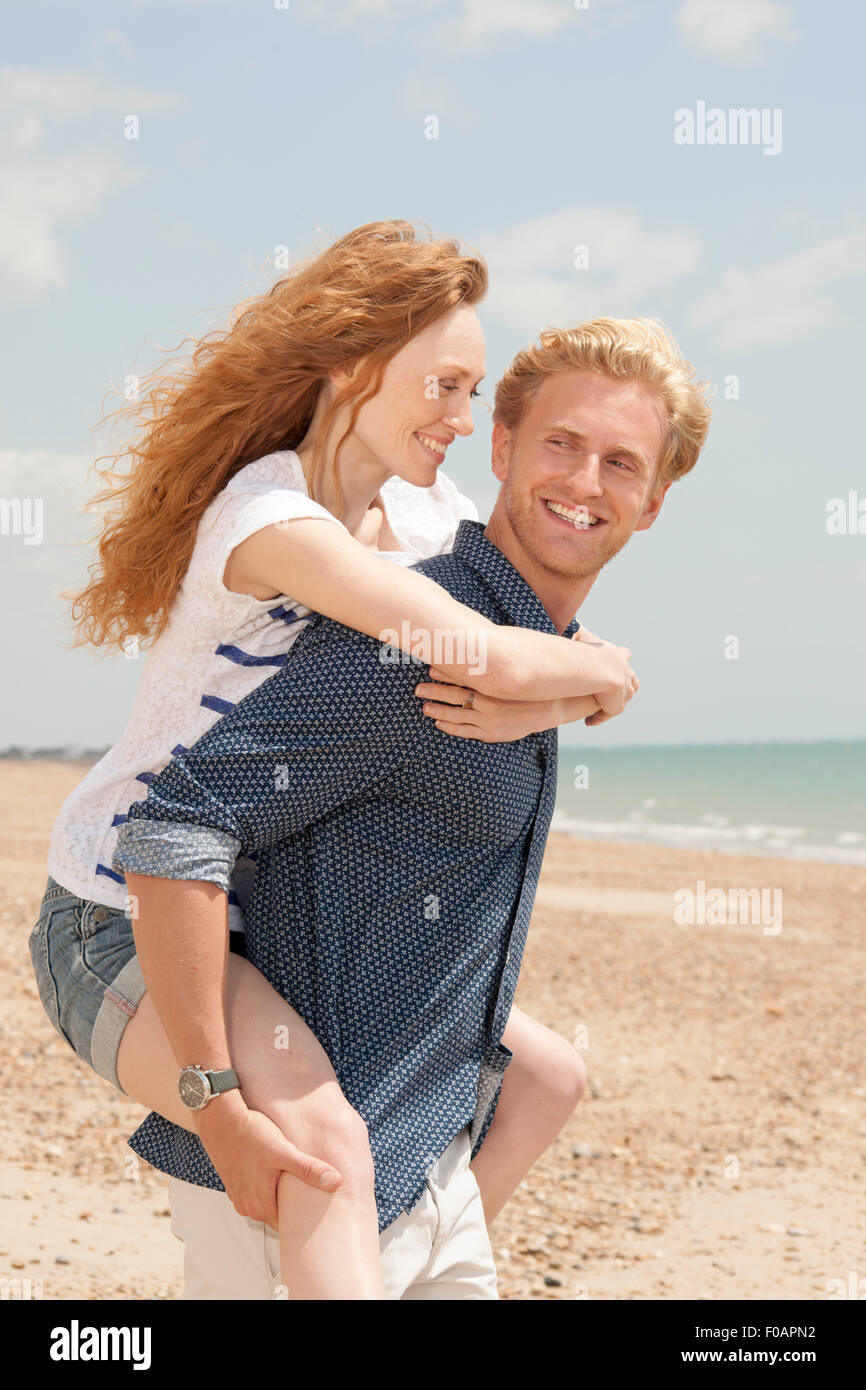man giving girlfriend a piggyback at the beach - Stock Image