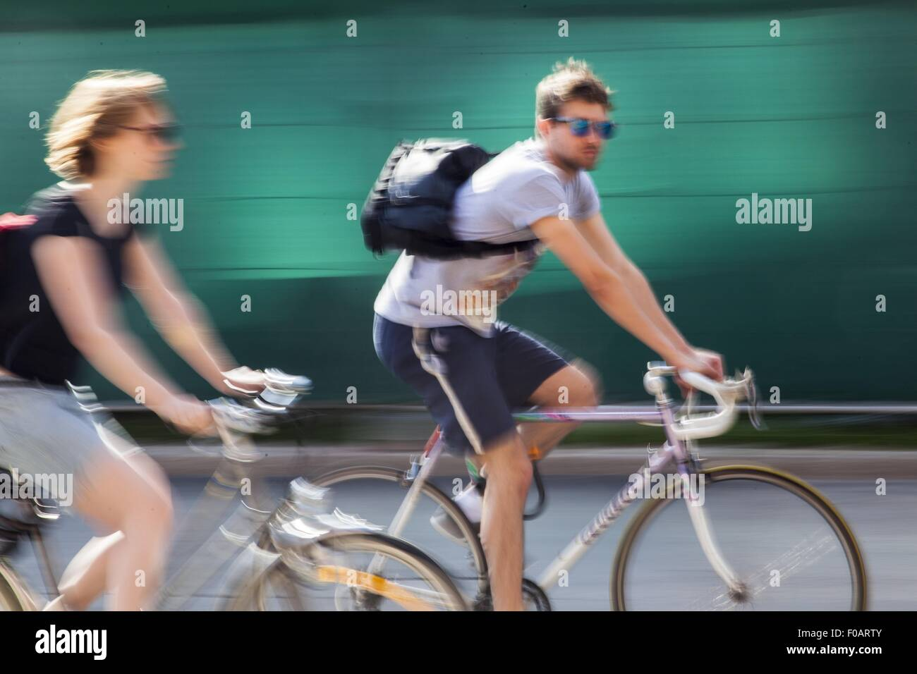 Woman riding bicycle, blurred motion, Freiburg, Germany - Stock Image