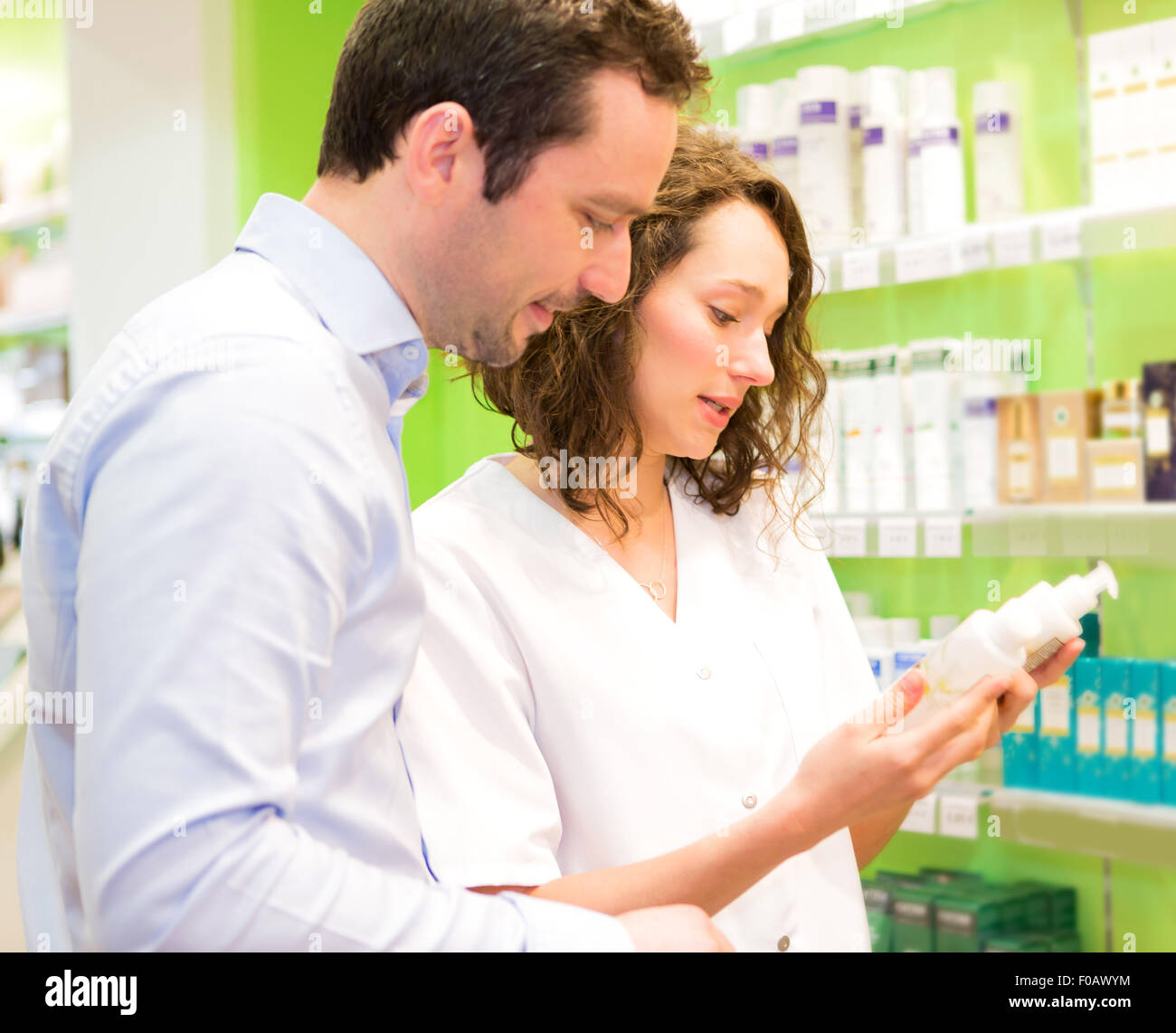 VIew of an Attractive pharmacist advising a patient - Stock Image