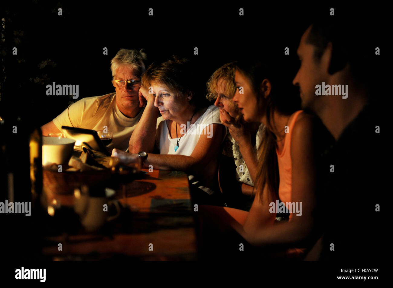 Family looking at an Apple iPad computer screen at night - Stock Image
