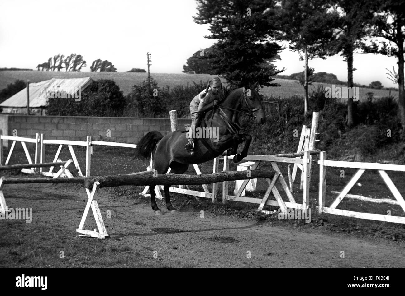 A girl practicing showjumping - Stock Image
