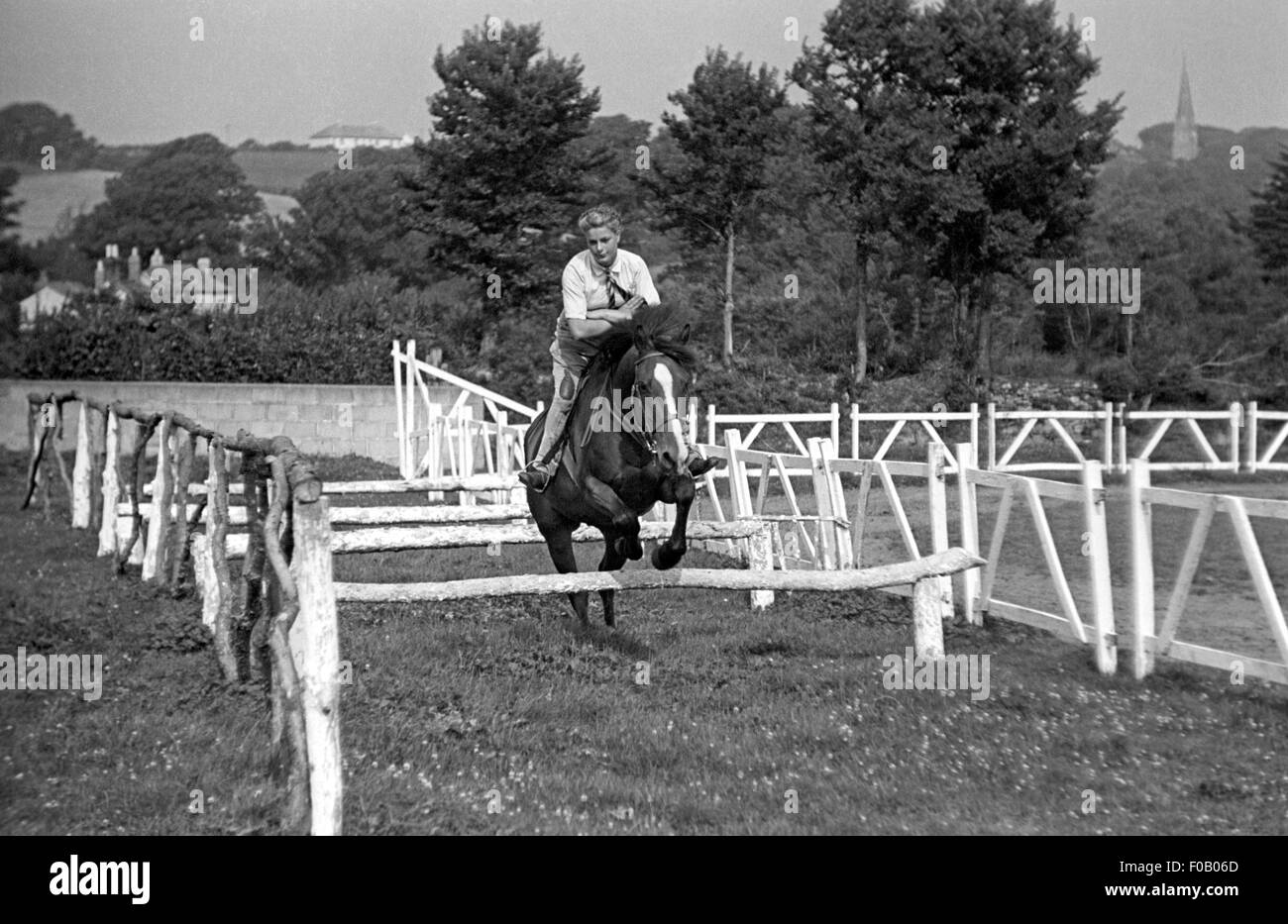 A teenage girl practicing showjumping - Stock Image