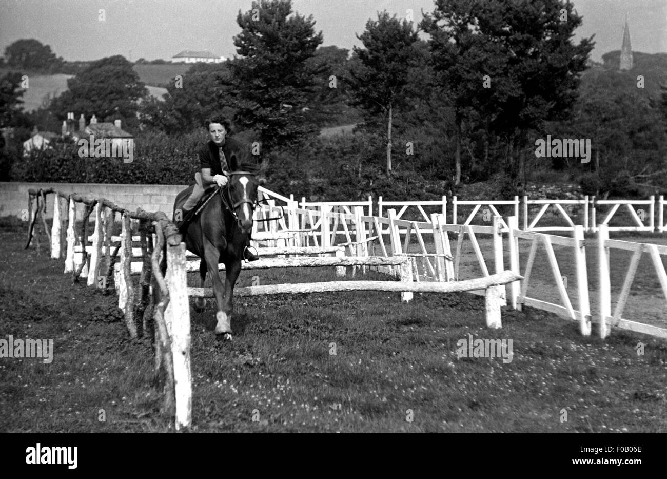 A woman practicing showjumping - Stock Image