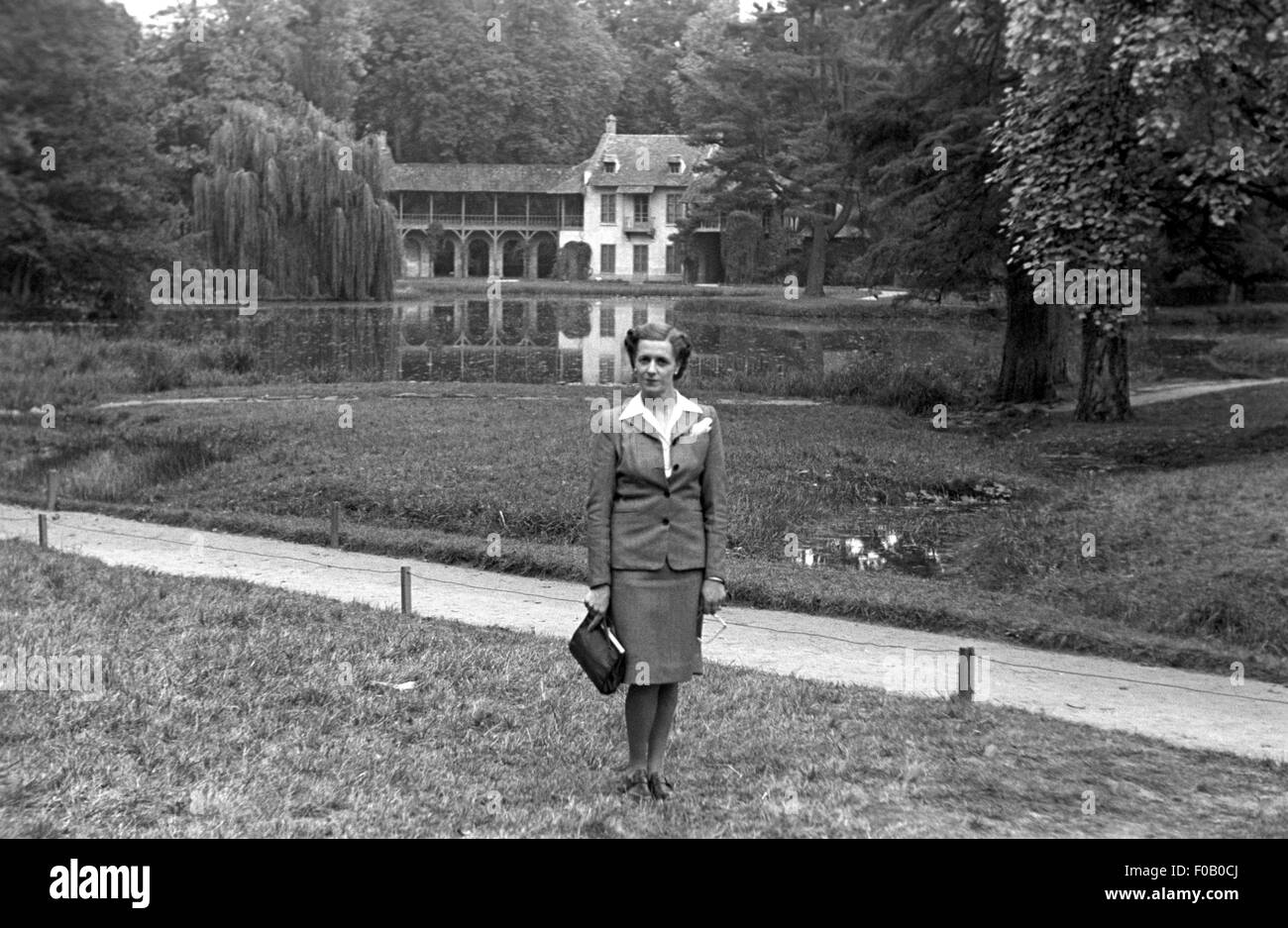A woman standing in front of the Queen's hamlet in Versailles - Stock Image
