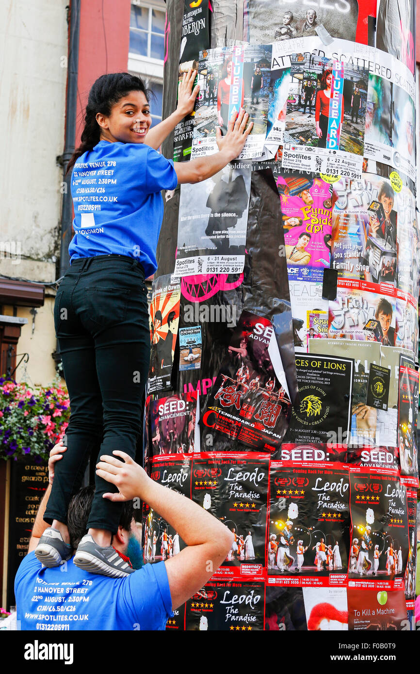 Rebecca Solomon from Spotlites theatre Group, standing on the shoulders of Lewis Colson, as she puts up adverts - Stock Image