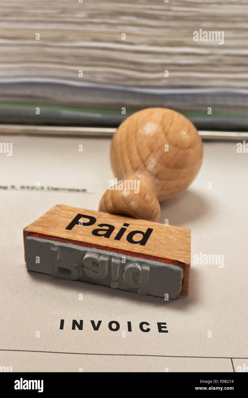 a stamp with the inscription paid is on an invoice - Stock Image
