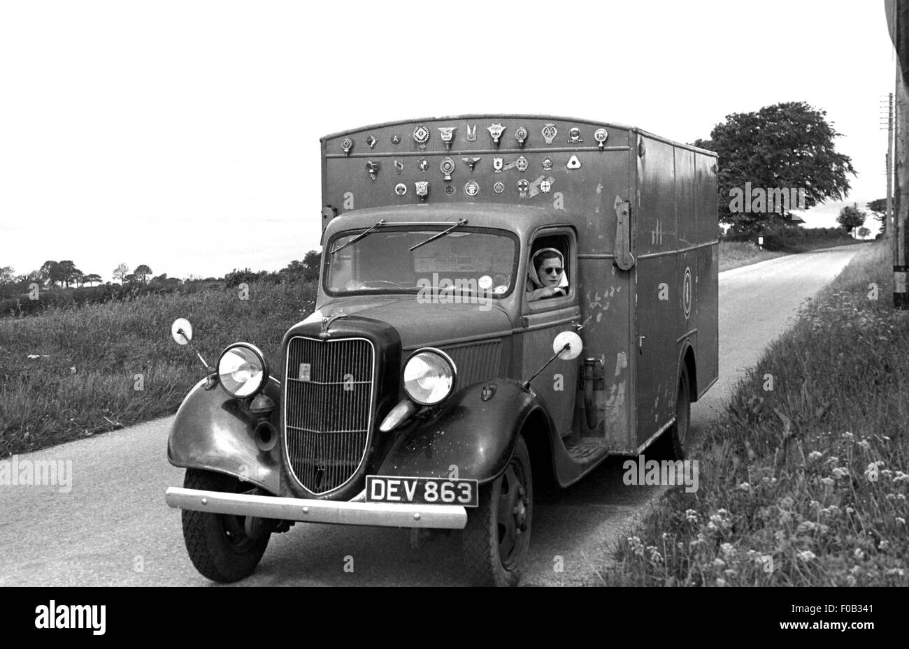 A woman leaning out of a van window parked on a country road - Stock Image