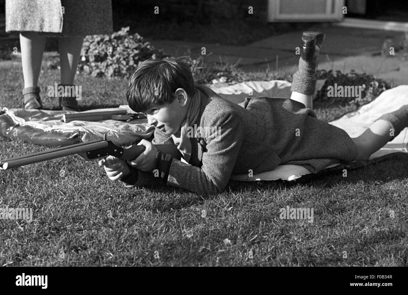 A young man with a rifle taking aim down the garden. - Stock Image