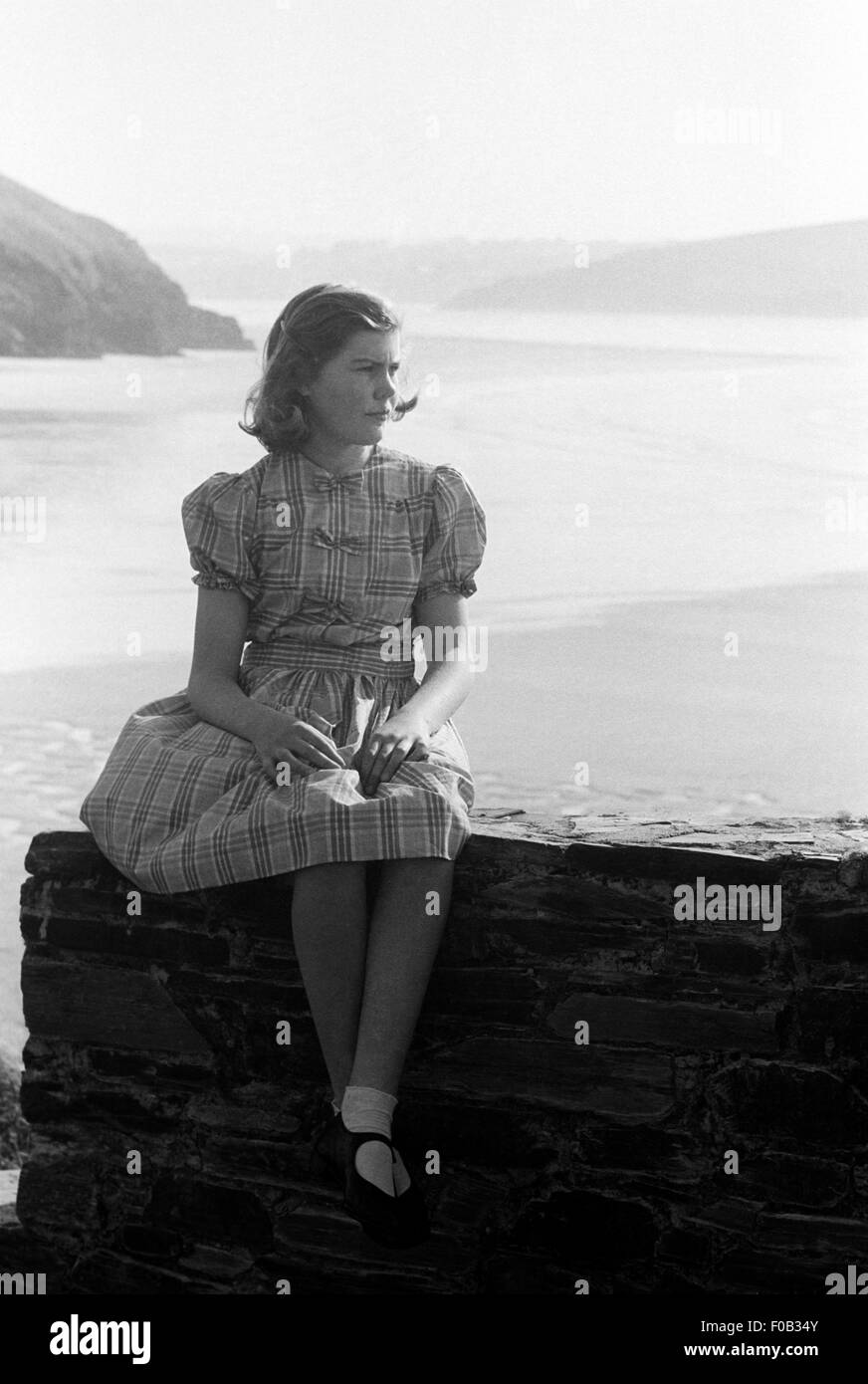 A young girl sitting on a wall at the seaside - Stock Image