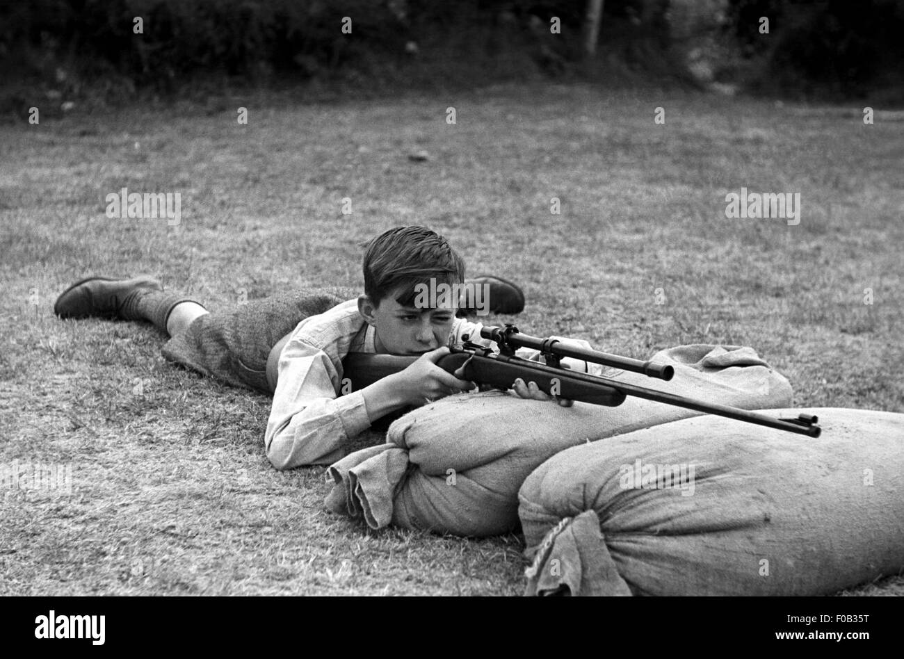 A young boy taking aim with his rifle as he rests on sand bags on the ground. - Stock Image