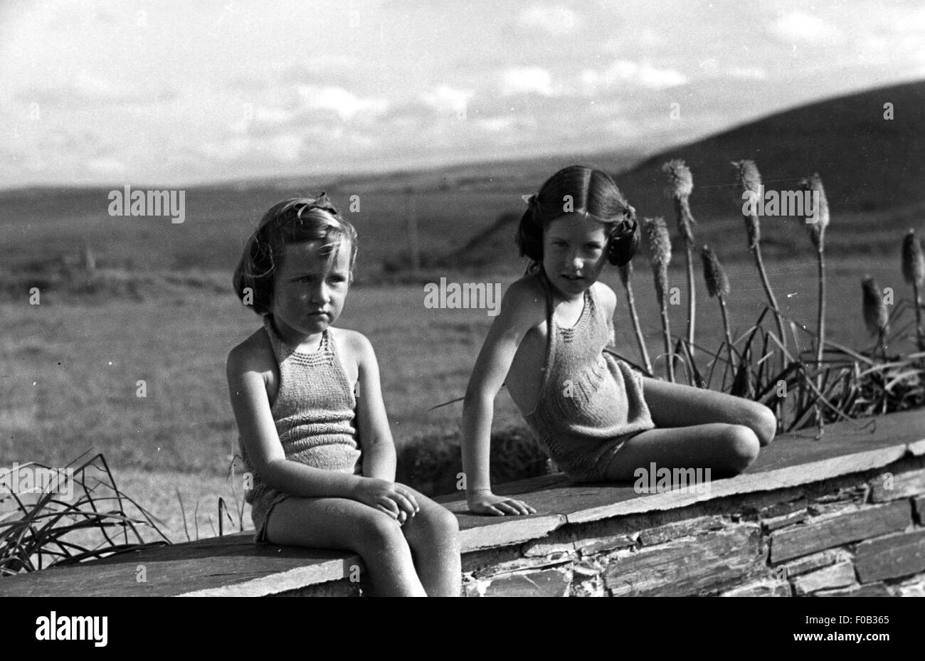 Two young girls in their bathing suits sitting on a garden wall - Stock Image