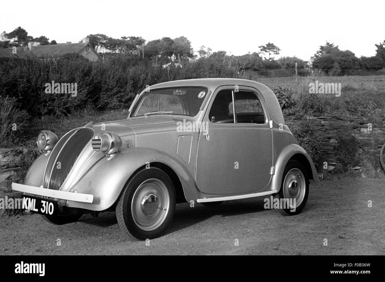 A Topolino Fiat 500 parked near a field. - Stock Image