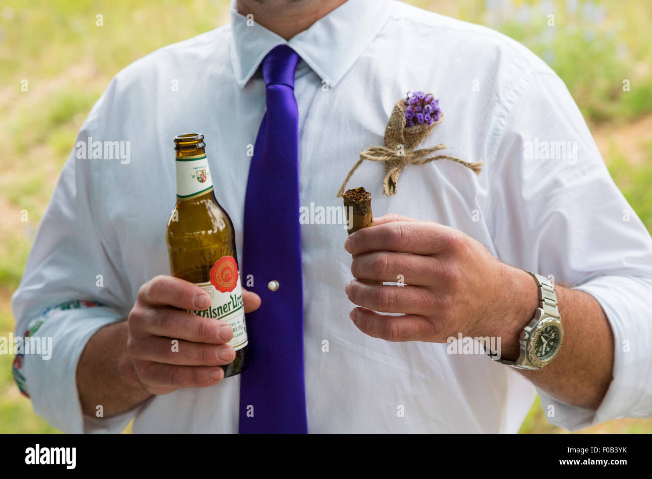 Dillon, Colorado - A man holds a beer and a cigar during a wedding celebration. - Stock Image
