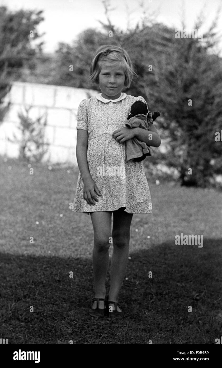 a girl holding a doll in the garden stock image - The Doll In The Garden