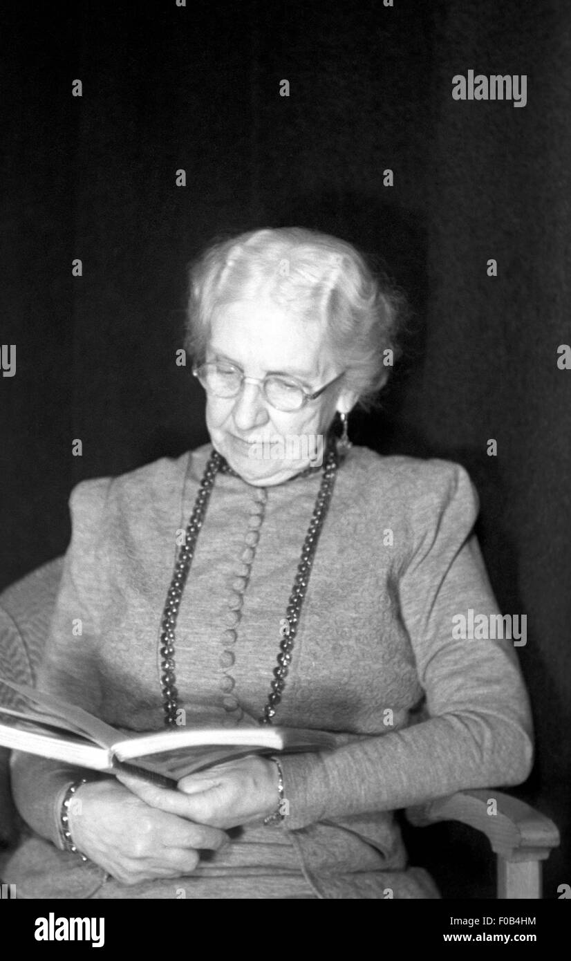 Old lady reading a book. - Stock Image