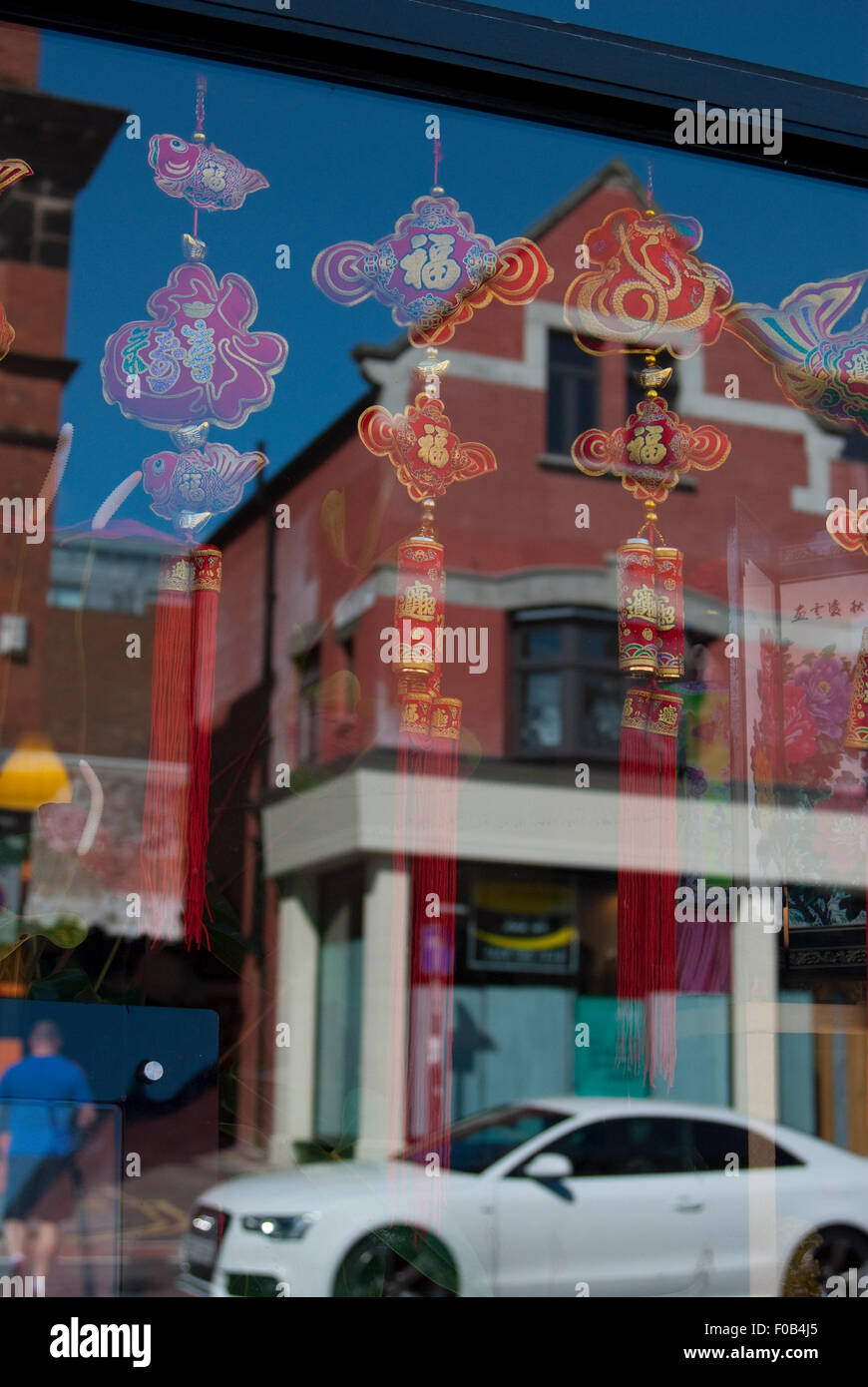 Editorial image taken in China town district of Liverpool of a car and building reflected in a window Stock Photo