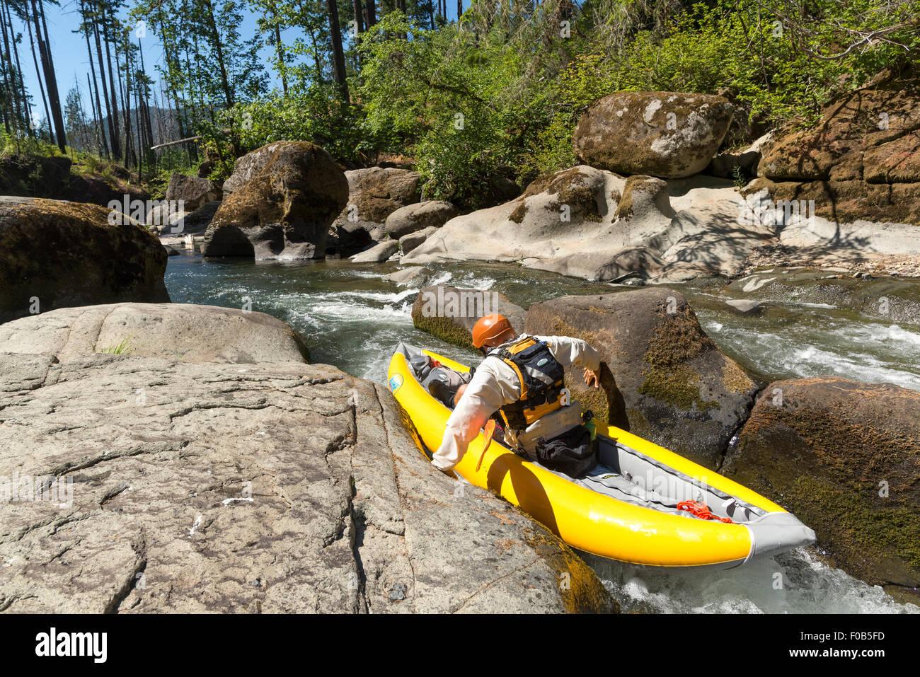 Paddler pushing wedged boat through a narrow shoot on Fall Creek, Oregon. - Stock Image