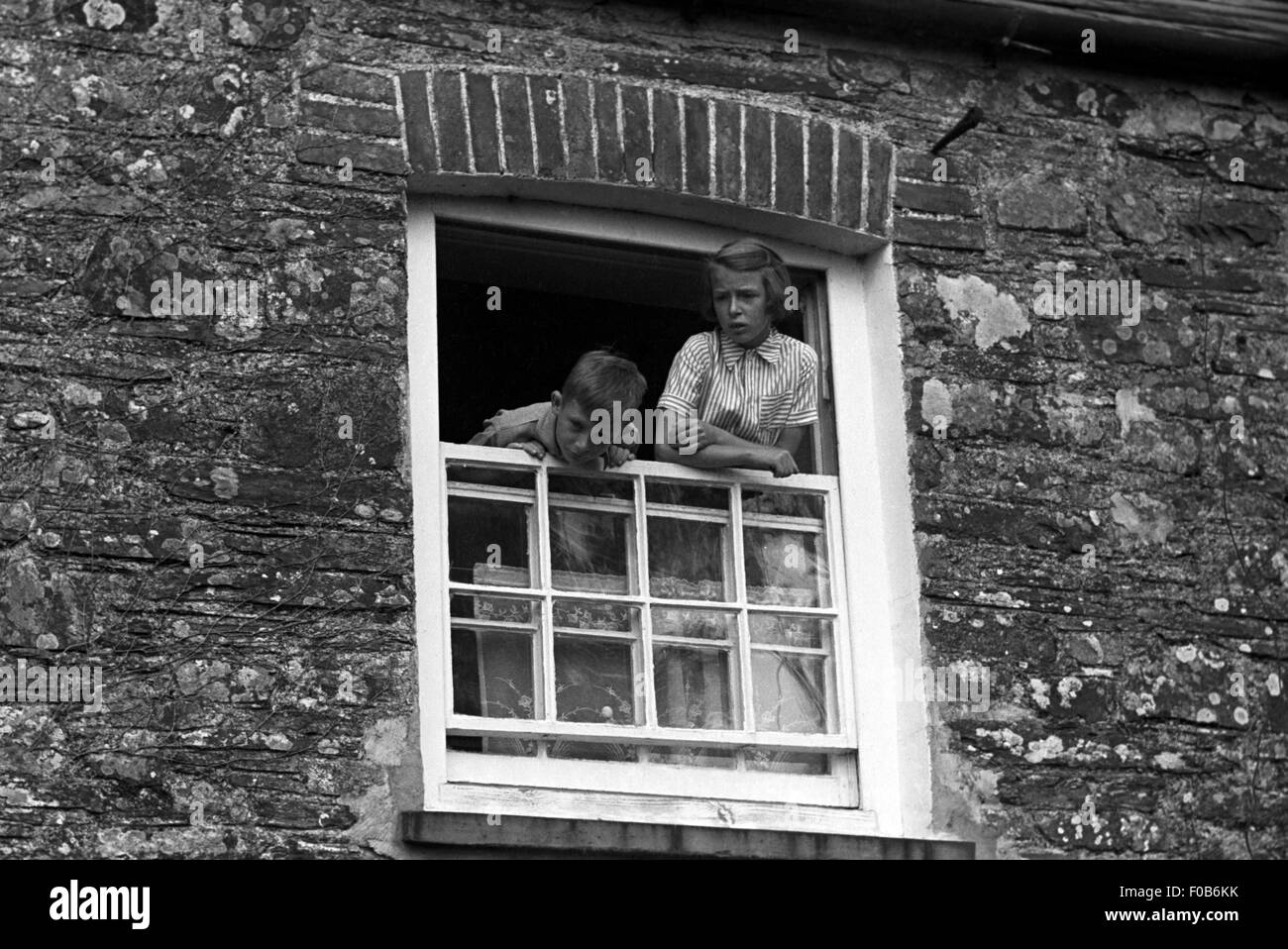 A view from below of a young boy and girl leaning out of an open window. - Stock Image