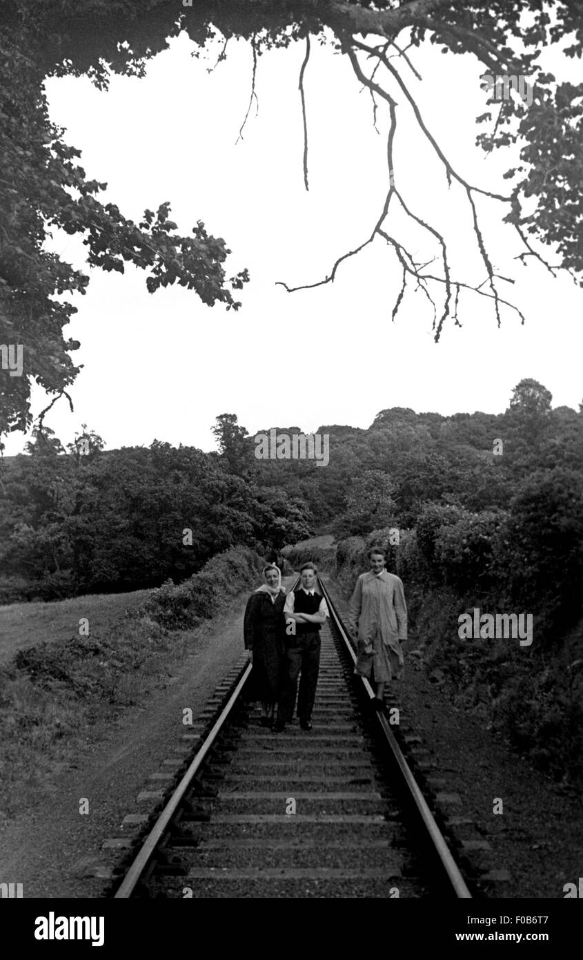 Two middle aged women and a young man standing on the train tracks in the country - Stock Image