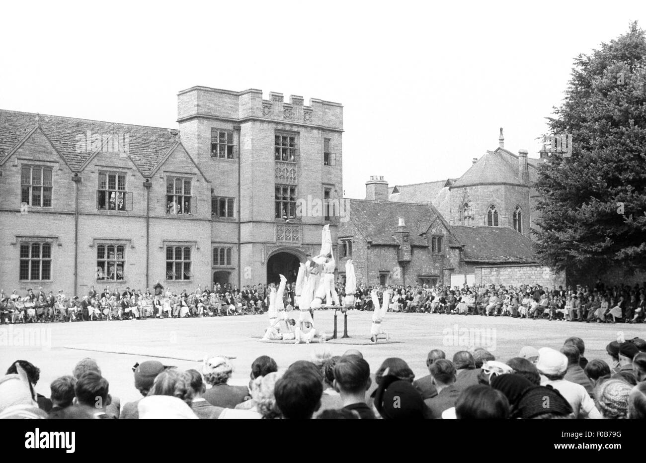 A group of men doing a gymnastic display watched by a large audience in a square outside a manor house. - Stock Image