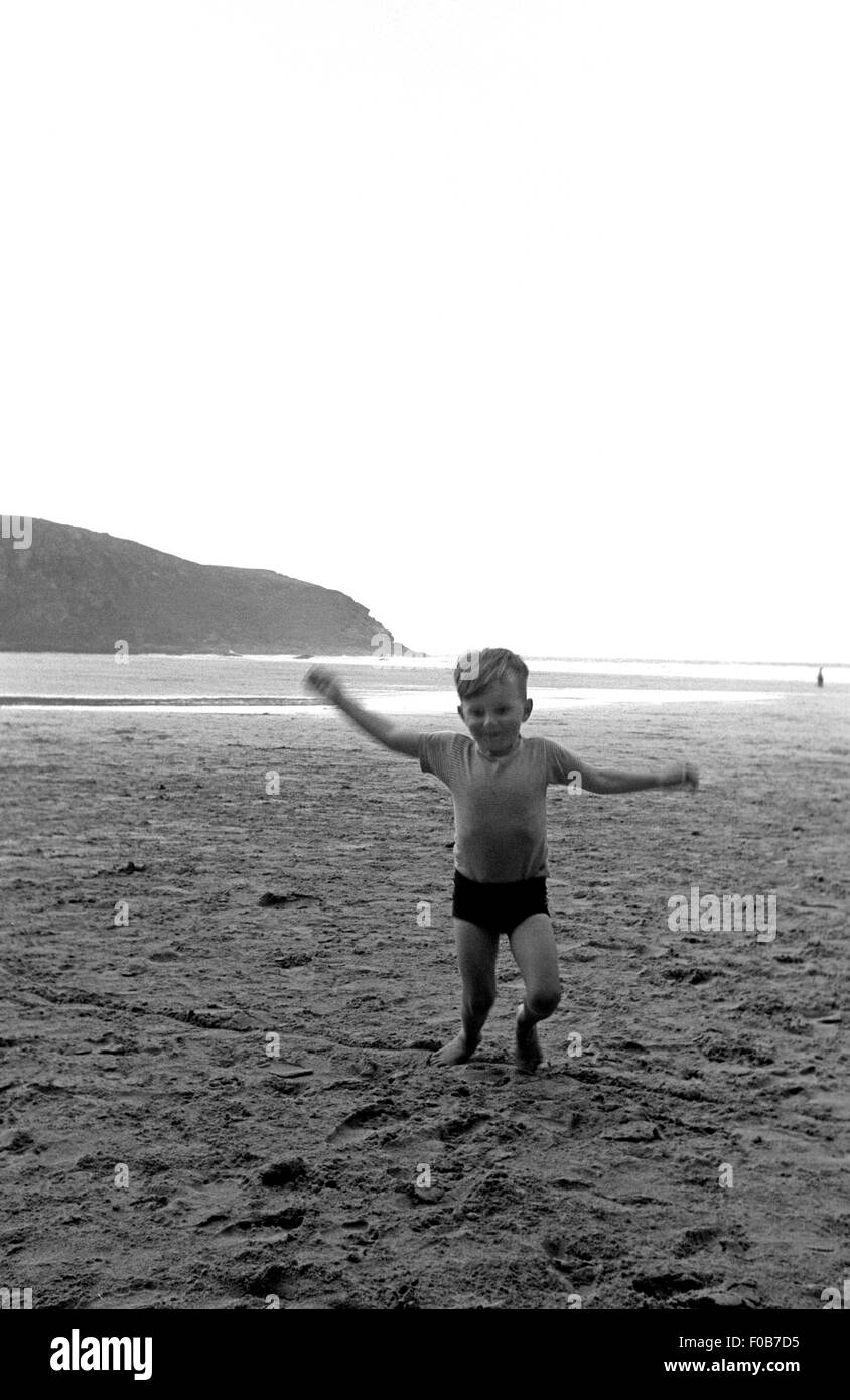 A young boy running on the beach - Stock Image