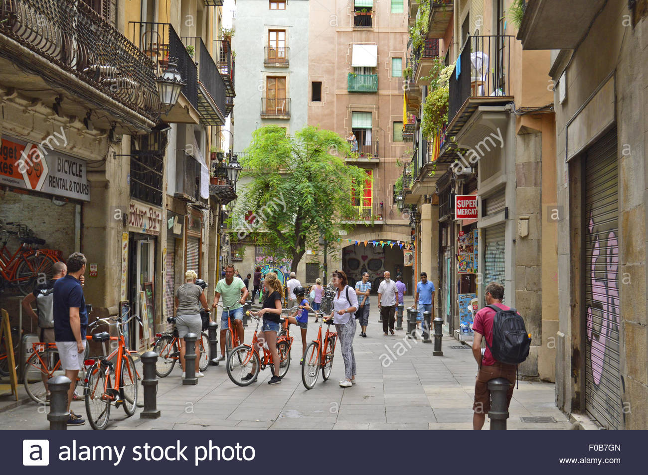 Tourists outside bicycles rental shop in Ciutat Vella district Barcelona Catalonia Spain Europe - Stock Image