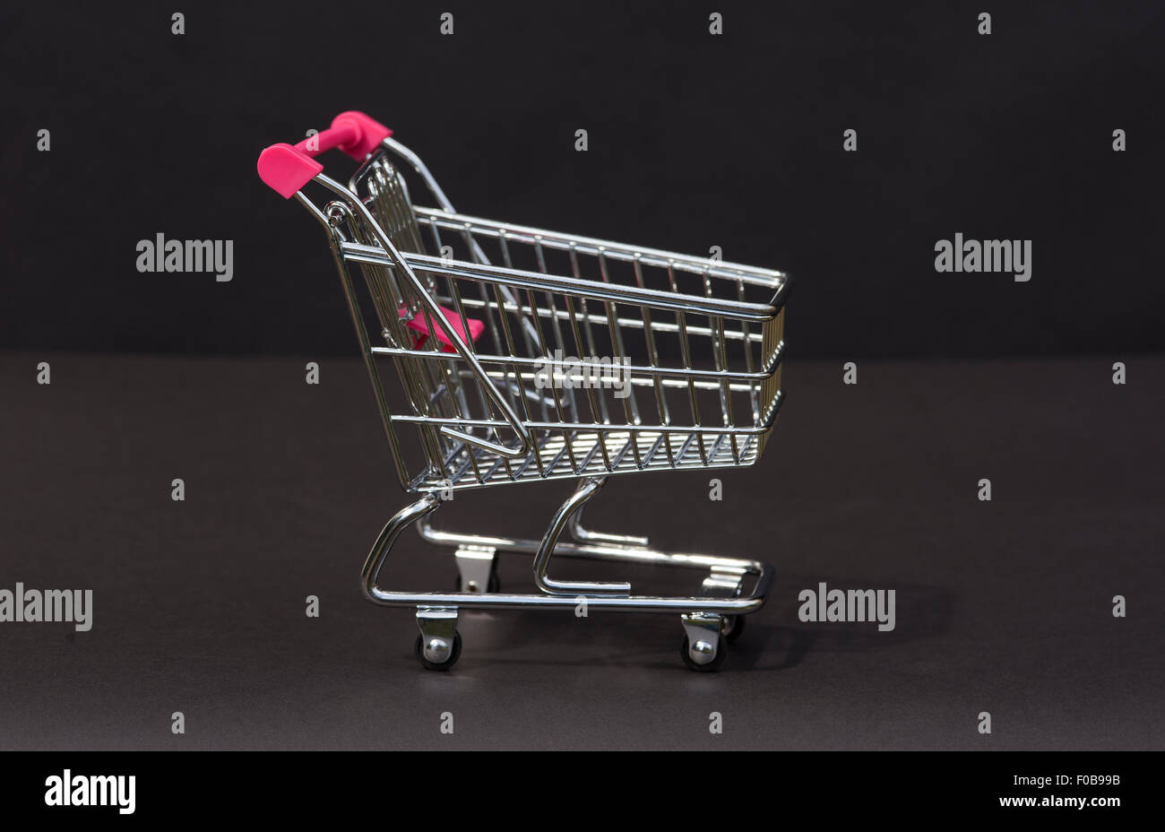 A tiny supermarket trolley in chrome - Stock Image