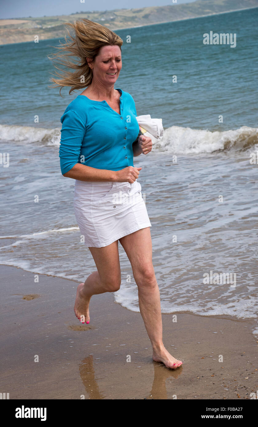 Woman with hair flowing running along the beach to keep fit - Stock Image
