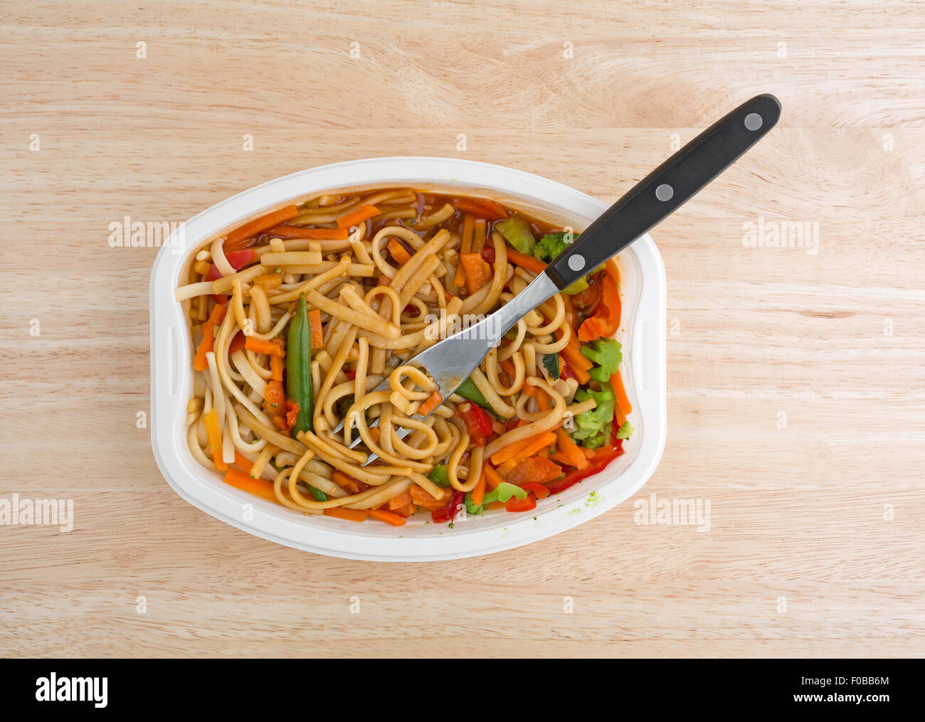 Top view of a TV dinner of noodles and vegetables in a white tray with a fork on a wood table top. - Stock Image