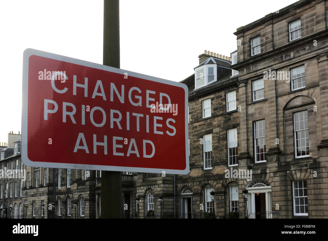 A sign reads 'Changed Priorities Ahead' in Edinburgh, Scotland. The sign stands close to Georgian buildings. - Stock Image