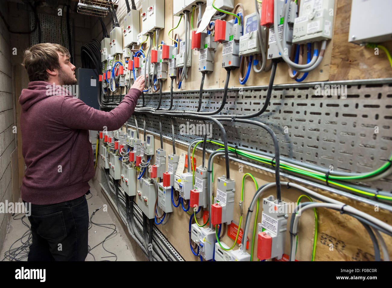 Man reading electricity meters, England, UK - Stock Image