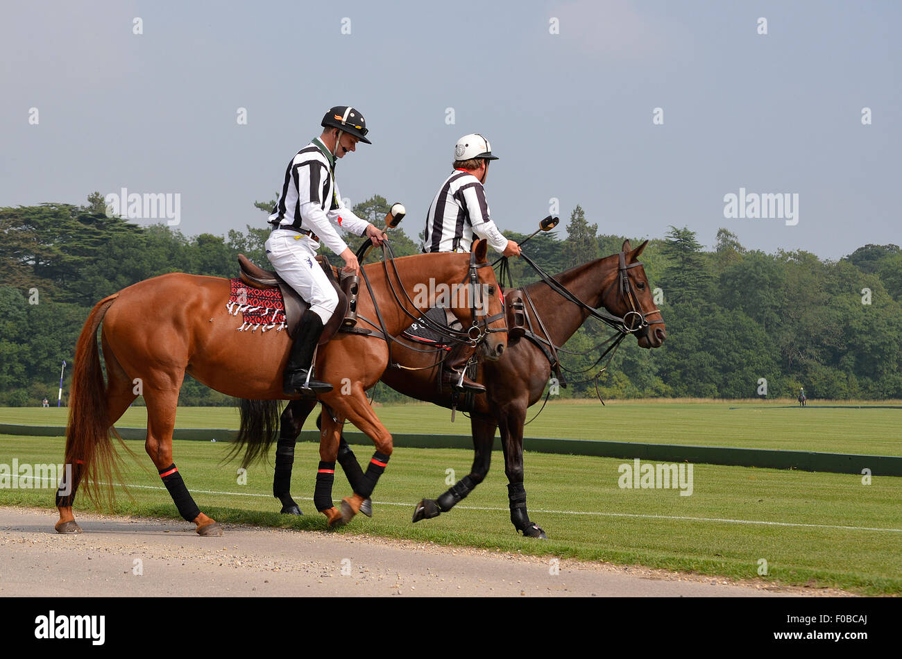 Two horse polo umpires on their horses at the Cirencester Park Polo Club in Cirencester, UK. - Stock Image
