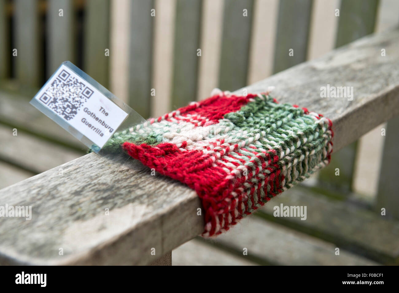 Guerilla Knitting street art on a bench in Burford Cotswolds Oxfordshire England UK Europe - Stock Image
