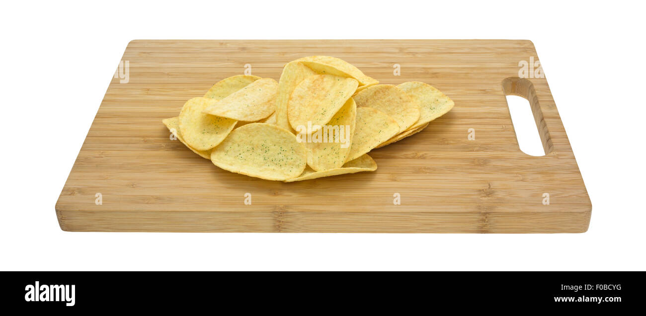A small serving of sour cream and chive flavored potato chips on a wood cutting board isolated on a white background. - Stock Image
