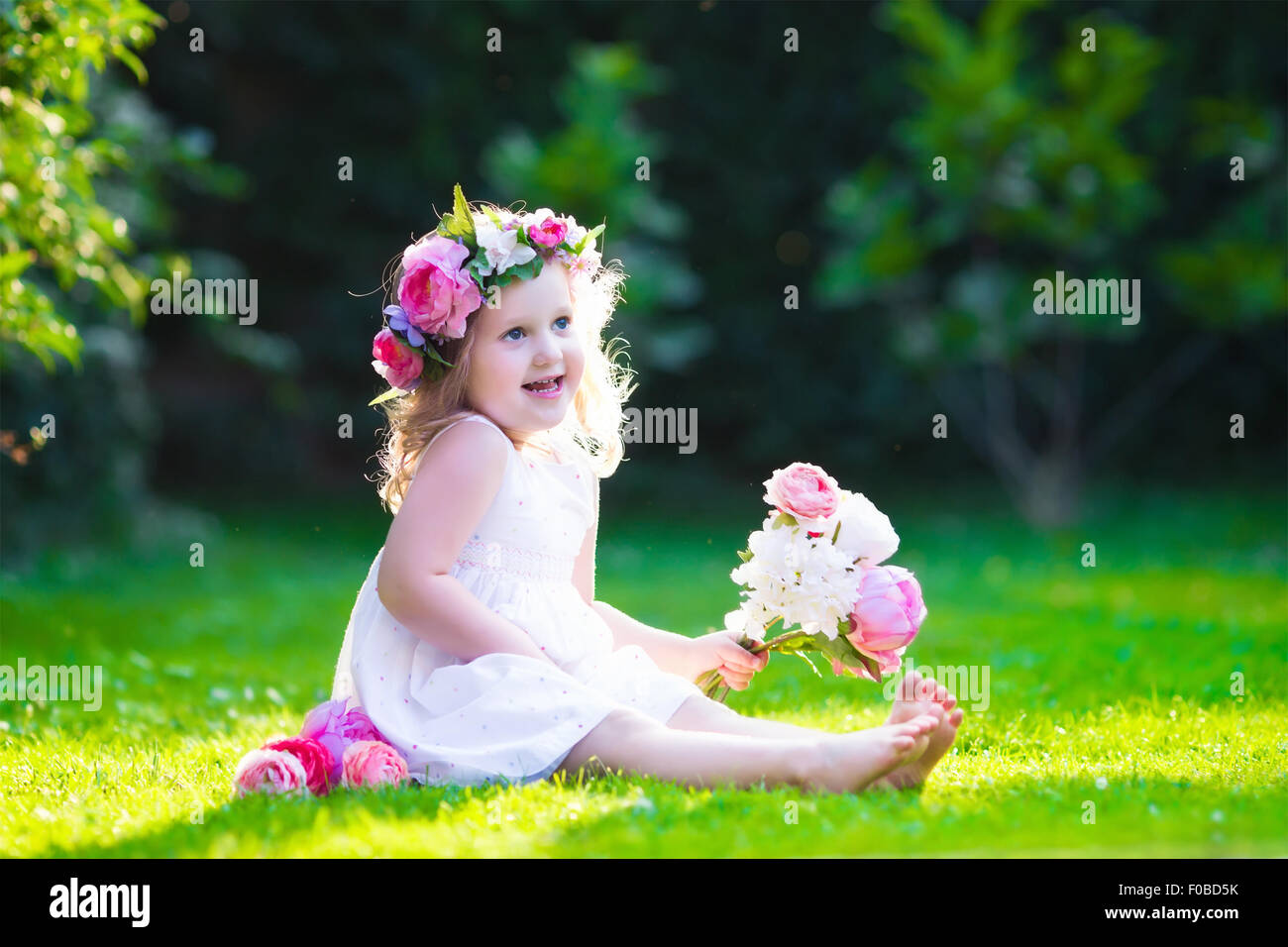 little cute girl with pink flowers. child wearing a white dress