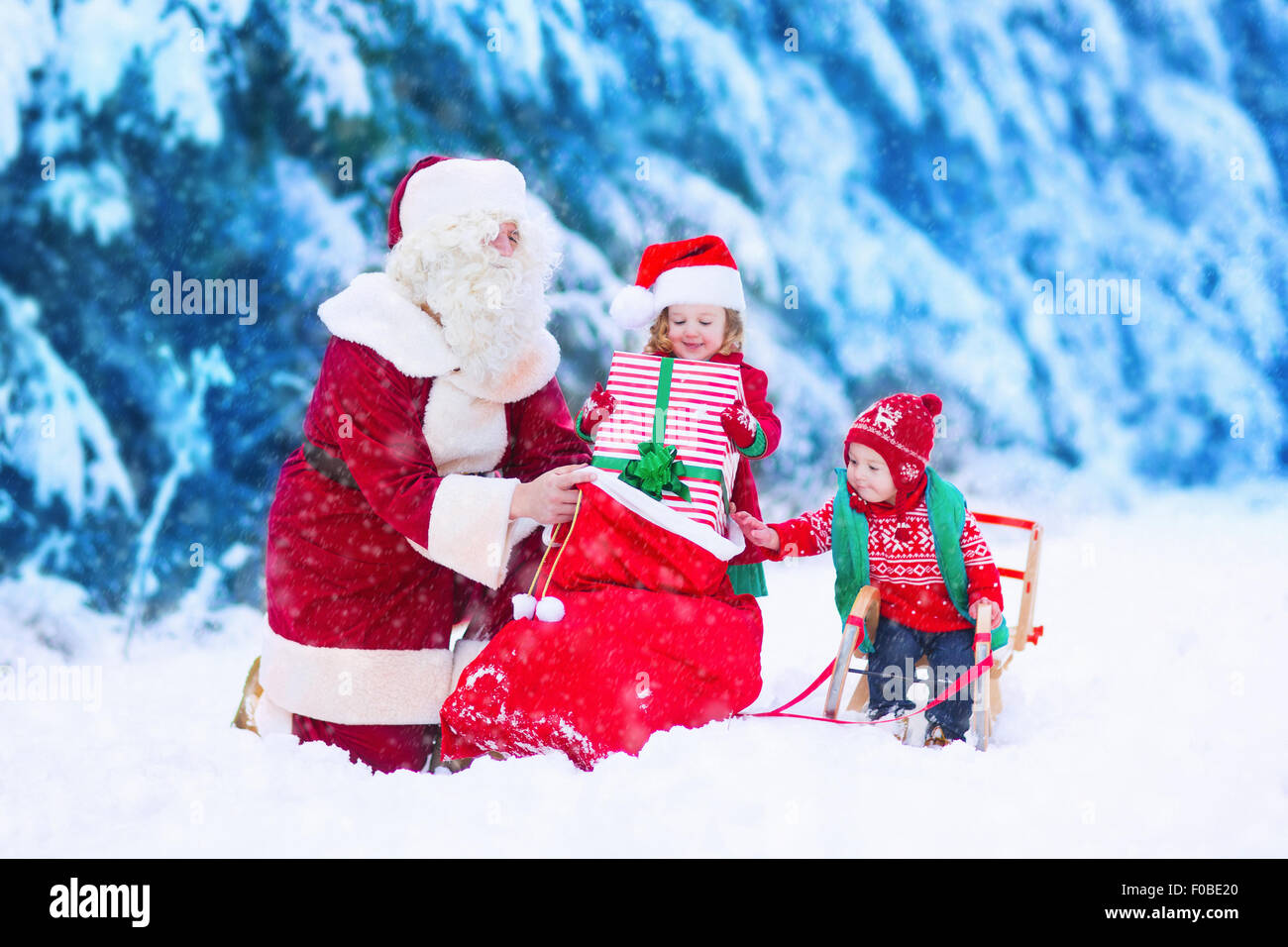 Santa Claus and children opening presents in snowy forest. Kids and ...