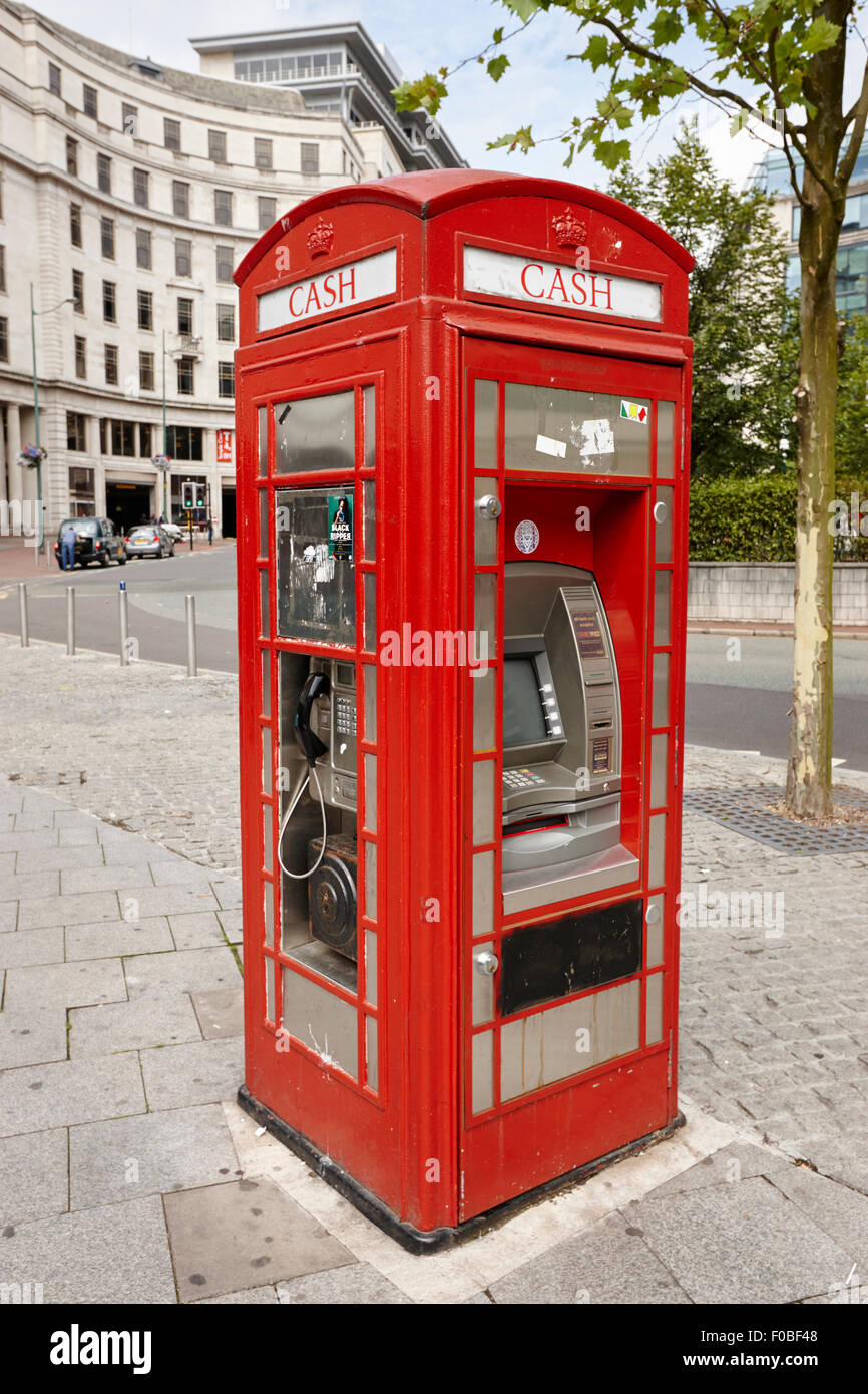 old red telephone box converted into a phone box and atm cash machine Birmingham UK - Stock Image