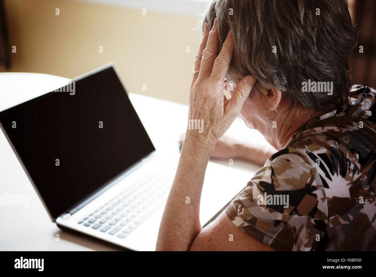 senior woman working on her laptop in her kitchen table Stock Photo