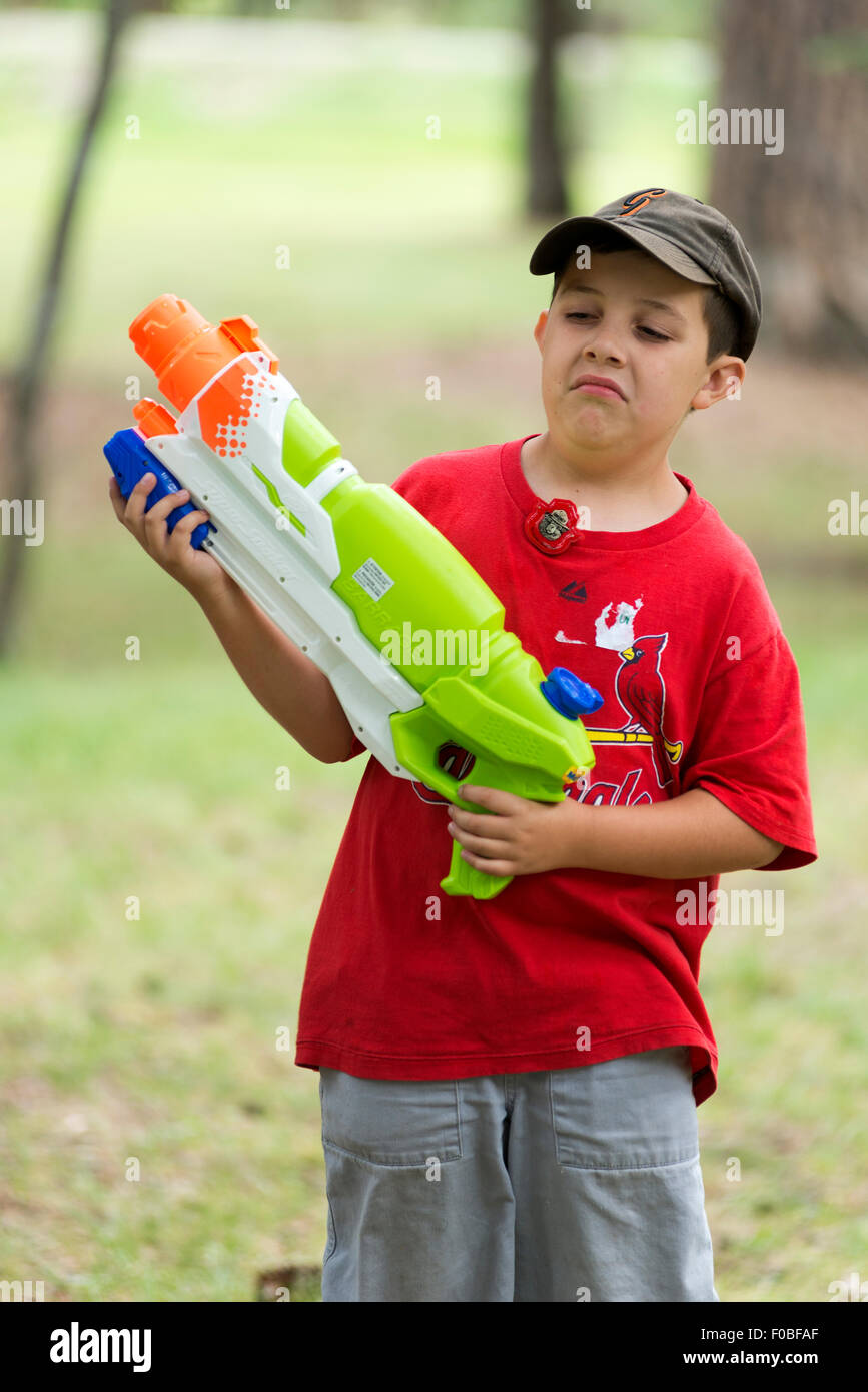 Boy with super soaker squirt gun. - Stock Image