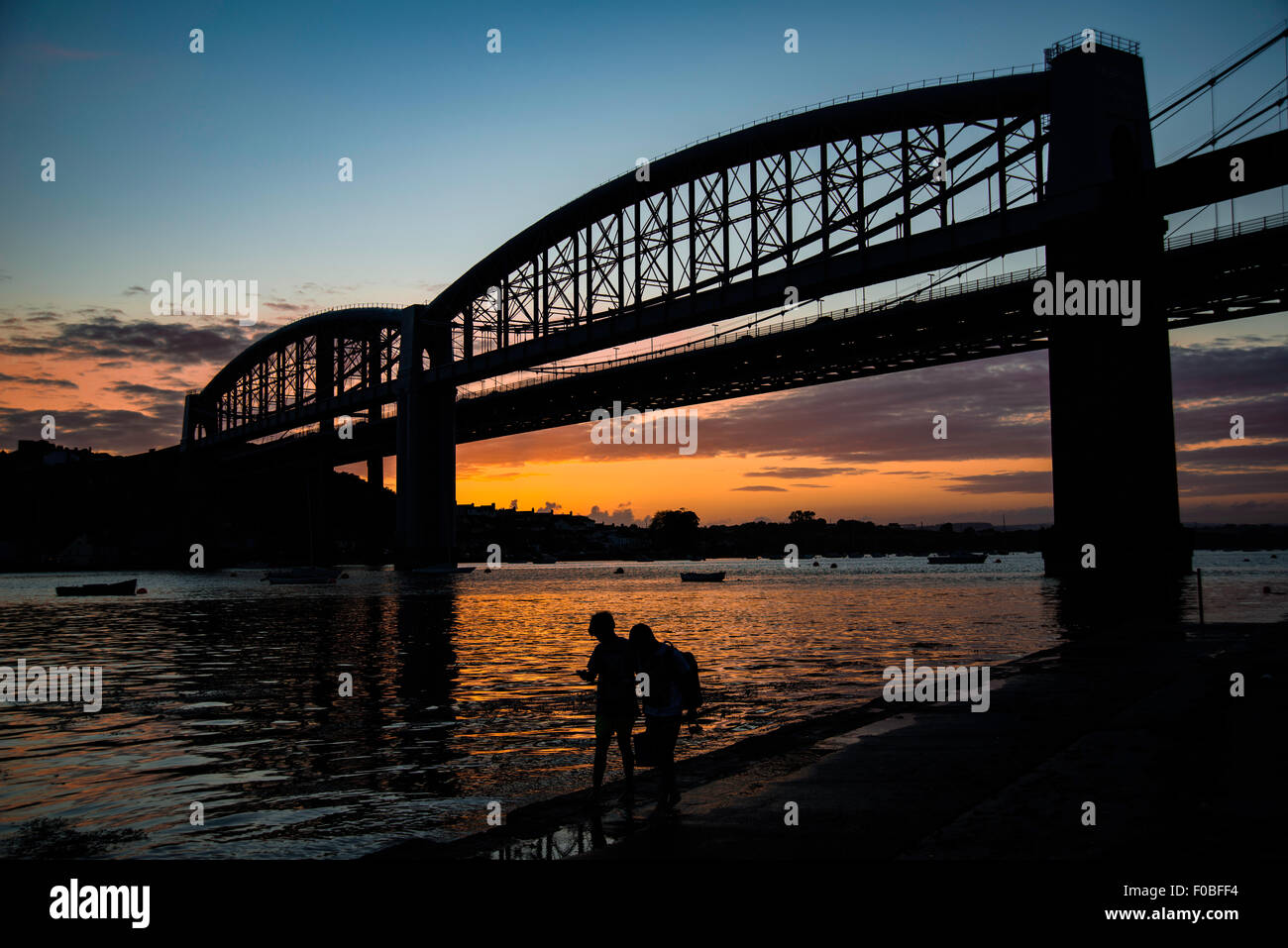 Two boys walking home along the river bank after a days fishing with the Albert Bridge and setting sun in the background. - Stock Image