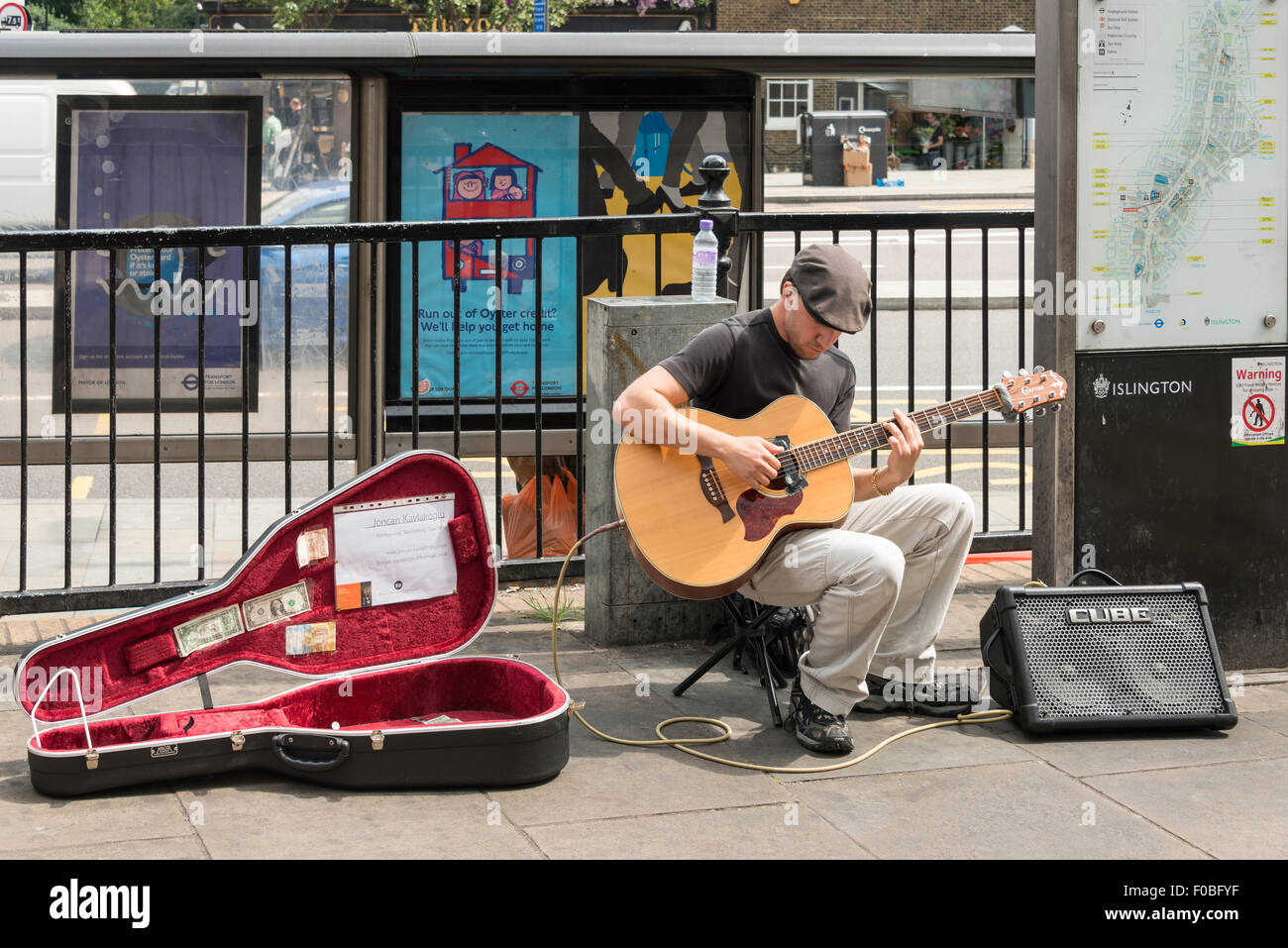 Street busker playing guitar, Islington High Street, Islington, London Borough of Islington, London, England, United - Stock Image