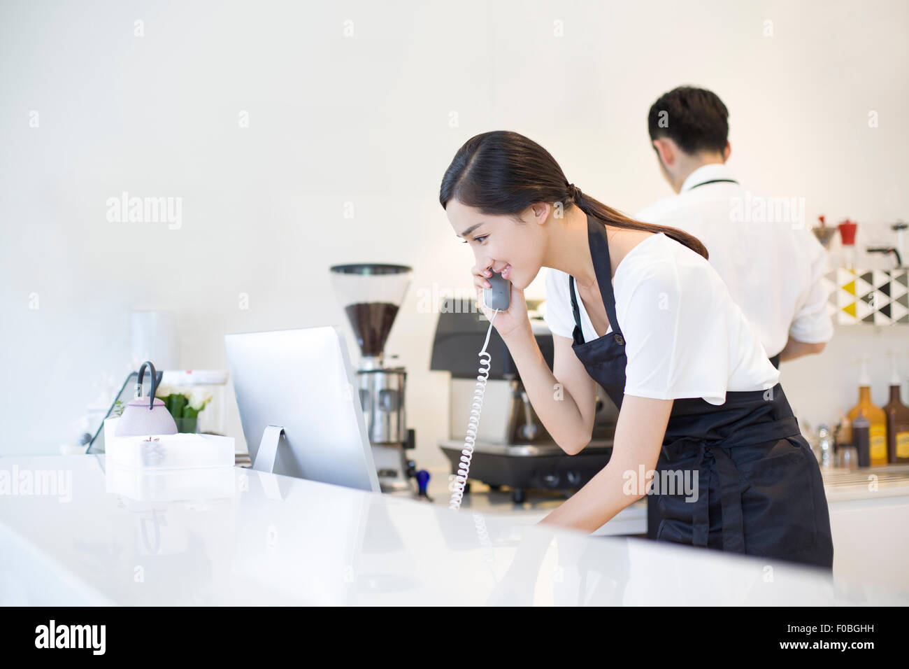 Coffee shop owner talking on the phone - Stock Image